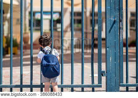 Kid With School Backpack Look On Schoolyard Towards An Open Entrance Or Exit Door. Schools And Presc