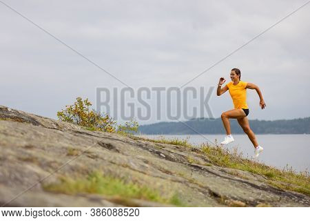 Side View Of Fitness Woman Doing High-intensity Running On Mountainside By The Sea