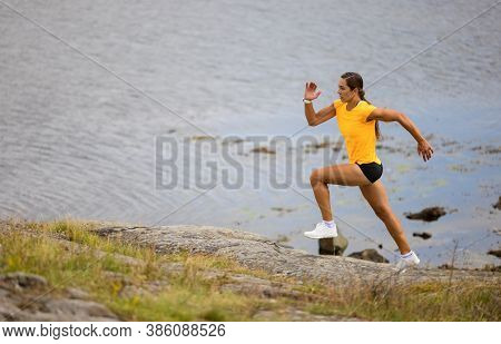 Focused Fitness Woman Doing High-intensity Running On Mountainside By The Sea