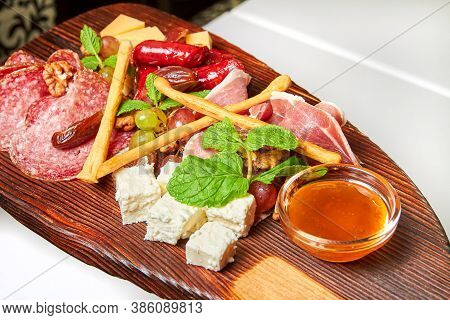 Assorted Cheeses And Meat Delicacies On Wooden Board. Close-up, Selective Focus