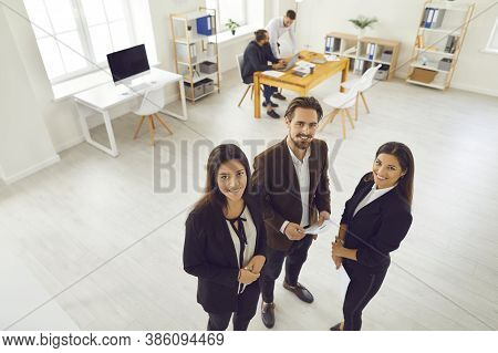 Aspiring Young Business Partners In Formal Wear Looking At Camera During Meeting In Modern Workspace