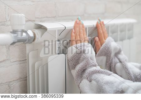 A Woman Wearing In Pajamas Warms Cold Hands On The Heating Radiator