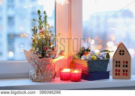 Christmas tree, Christmas decorations, candles and Christmas gifts on a window sill