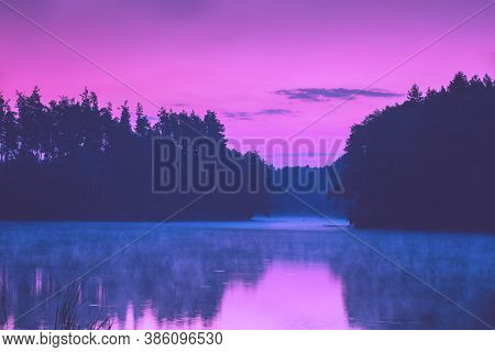 Magical Purple Sunset Over The Lake. Serene Lake In The Evening. Nature Landscape