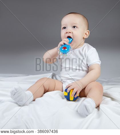 Image Of A Ten-month-old Baby With Rattle And Ball