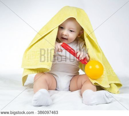 Photo Of A Eleven-month-old Baby With Rattle And Towel