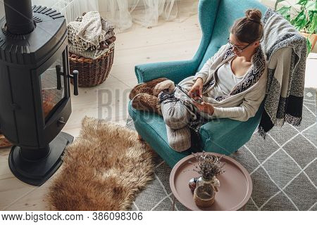 Woman By The Fireplace, Sitting In A Cozy Armchair, With A Warm