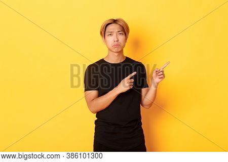 Portrait Of Disappointed And Sad Handsome Blond Asian Guy, Sulking Upset, Pointing Fingers Upper Rig