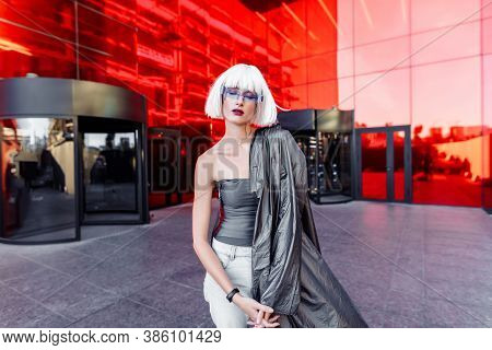 Futuristic Style. Woman With Glasses And Near A Red Futuristic Building.