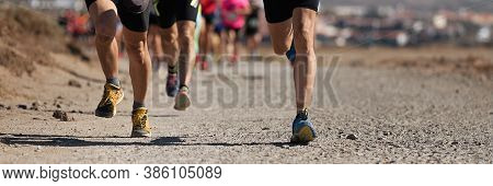 Runners Running Shoes On Trail Run. Ultra Running Athletes Legs Close Up On Running In Rock Path Tra