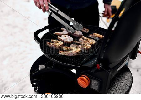 Man Grilling Delicious Fish On A Portable Bbq, Snowy Winter Barbecue Outdoors In The Cold .