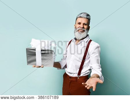 Bearded Man In A White Shirt, Brown Pants And Suspenders. Smiling, Reaching Out To You, Holding Gift