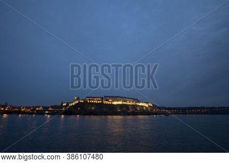 Petrovaradin Fortress In Novi Sad, Serbia, On Danube River, On A Cloudy Autumn Night Evening. It Is