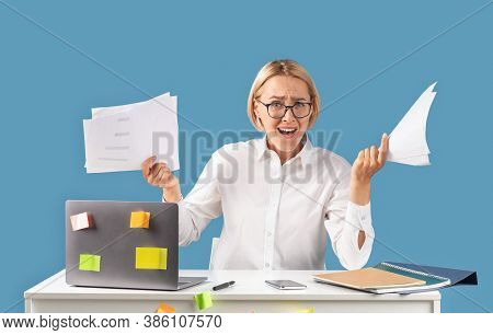 Stressed Businesswoman With Papers Feeling Angry Or Having Nervous Breakdown Near Laptop At Desk, Bl