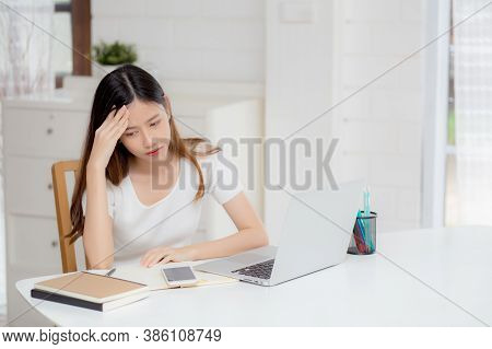 Young Asian Woman Headache During Working On Laptop Computer With Deadline On Desk At Home, Business