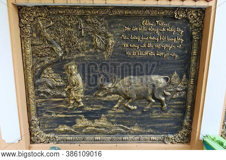 Hoi An, Vietnam, September 20, 2020: Bronze Relief Of A Monk Pulling A Buffalo In The Garden Of The
