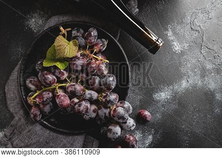 Purple Grapes On A Plate And Wine Bottle On A Dark Background.  Overhead View With Copy Space
