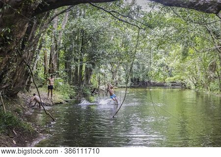 Northern Territory, Australia - March 18th, 2020: Teenagers Frolicking In A Shady Creek, Running Thr
