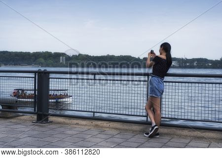 A Chinese Woman Taking Pictures Of A Tourist Boat On The Saint Lawrence River At The Old Port In Mon