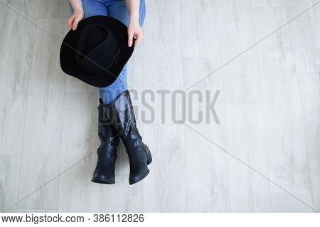 Woman Legs In Black Cowboy Boots With A Cowboy Hat. Sitting On A Gray Wooden Background.