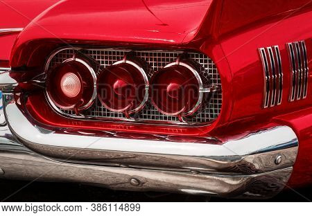 Rear Part Of Exterior Of A Red Old Timer Luxury Sports Car With Tree Tail Lights Framed In Chrome No
