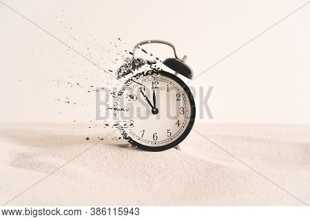 Concept Of Passing Away, The Clock Breaks Down Into Pieces. Analog Clock In The Sand, With Dispersio