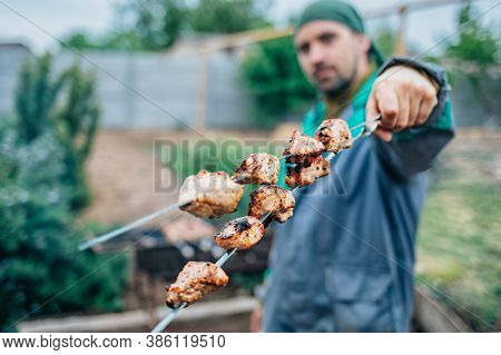 A Man Fries Kebabs On The Grill In His Infield.