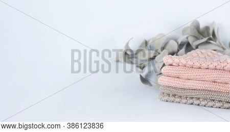 Pile Of Pink Knitted Cashmere Scarves, Sweaters On Light Blue Background. Folded Autumn And Winter C