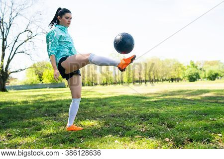 Young Woman Practicing Soccer Skills With Ball.