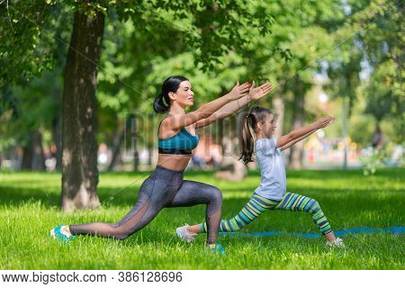 Girls Are Excercising In Park. They Are Stretching Together. Mom Ang Daughter. Side View.