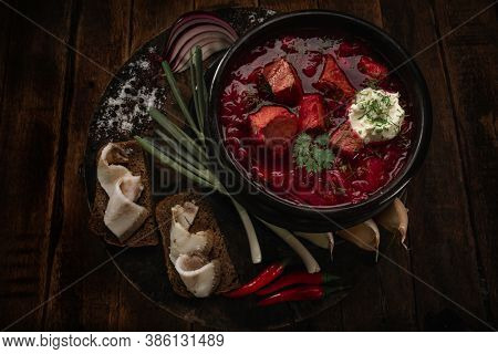 Traditional Ukrainian Russian borscht or red soup in the bowl on dark wooden background. Traditional ukrainian soup (borscht) with chilli, garlic, sour cream  and rye bread with bacon. Top view