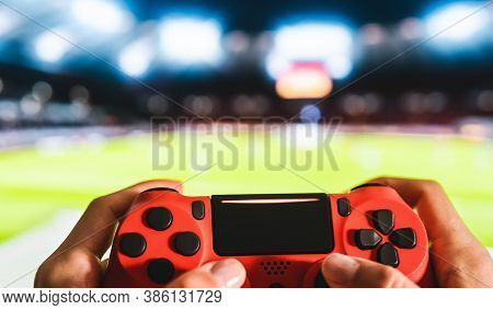 Young Man Having Fun Playing Online Soccer Video Games - Close Up Red Magma Game Pad On Tv Backgroun