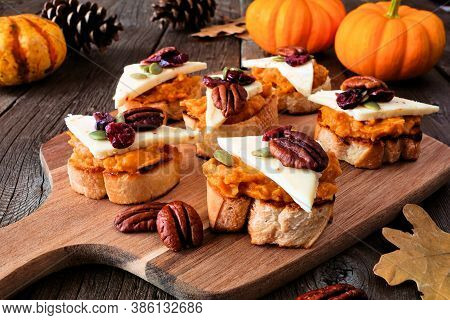 Autumn Crostini Appetizers With Pumpkin Spread, Cheese And Nuts. Side View Serving Scene On A Rustic