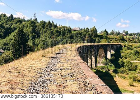 Panorama View Of Ancient Bridge. Viaduct With Old Railway Tracks Near Green Hill Of Mountain Forest.
