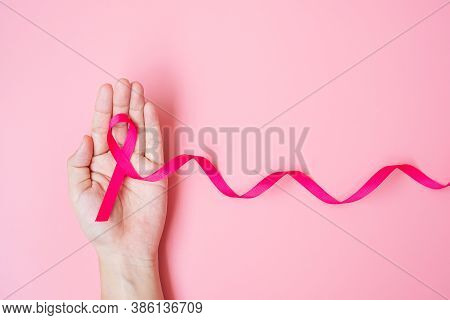 October Breast Cancer Awareness Month, Adult Woman Hand Holding Pink Ribbon On Pink Background For S