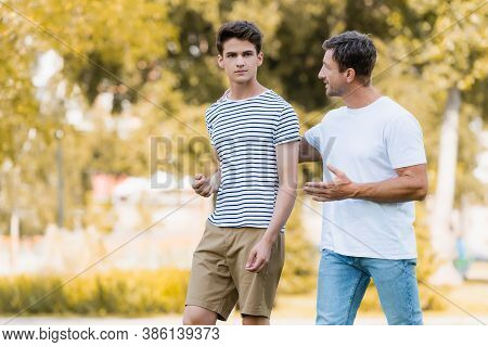 Father Walking, Gesturing And Talking With Teenager Son In Park