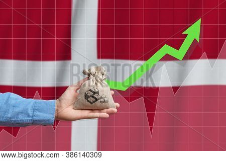 The Concept Of Economic Growth In Kingdom Of Denmark. Hand Holds A Bag With Money And An Upward Arro