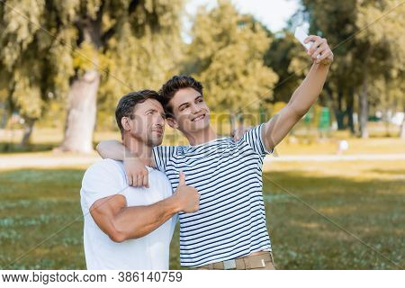 Father Showing Thumb Up While Teenager Son Taking Selfie In Park
