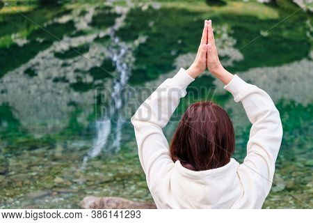 Young Woman Practicing Yoga And Meditating On The Lake Shore With Transparent Water And Reflected Wa