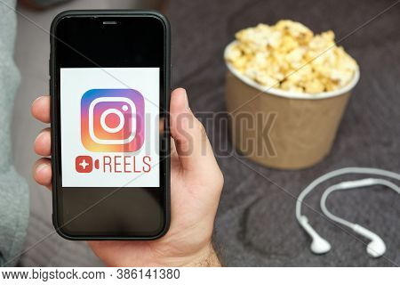 Reels Logo On The Mobile Phone Screen With Popcorn Box And Apple Earpods On The Background, Septembe