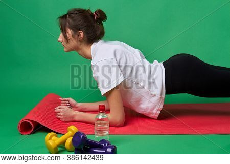 Slender American Girl Is Doing Plank Exercise. Attractive Young Woman Is Having Daily Workout On A R