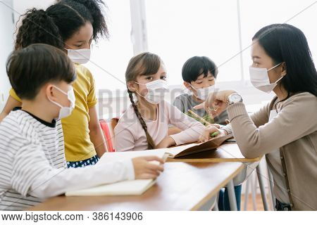 Group Of Diverse Elementary School Pupils And Female Asian Teacher Wearing Medical Mask At Elementar
