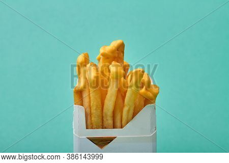 Close Up Fries With Yellow Sauce In A Pack Of Cigarettes. Concept On Unhealthy Harmful Food. Isolate