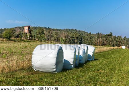 Landscape With Hay Bales In Plastic Wrap. Agricultural Landscape In The Czech Republic. Hogs Watchto