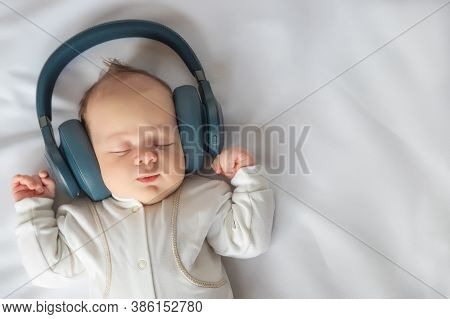 Newborn Baby Smiling Listening To Music With Headphones And Lying On White Sheet In The Crib, Happy