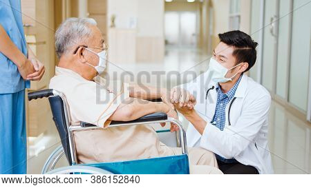 Young Male Asian Doctor Crouch Down Holding Hand And Talk To The Senior Adult Patient On Wheelchair