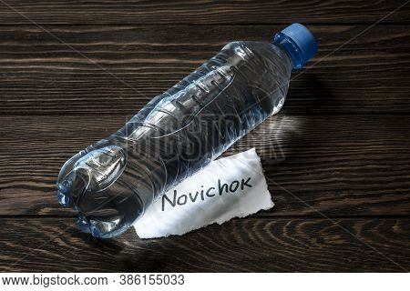 Bottle Of Water And Note Novichok On Wooden Table. Novichok Is Agent Poison, Deadly Nerve Venom. Con