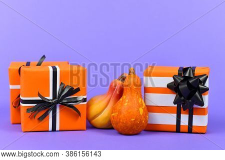 Gift Boxes With Traditional Halloween Event Colors Orange, Black And White And Small Ceramic Pumpkin