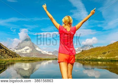 Mount Matterhorn And Swiss Alps Are Reflected On Riffelsee Lake. Tourist Woman Enjoying During Riffe
