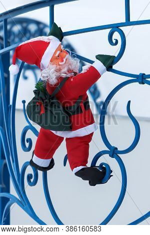 Toy Santa Claus Climbs With A Bag Of Gifts On The Balcony Of The Cottage Along The Railing